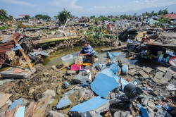 A woman sits amid the debris caused by the deadly Palu quake-tsunami that has so far claimed more than 1,400 lives
